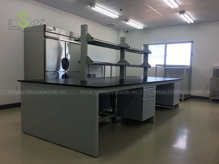 Bàn thí nghiệm trung tâm có kệ 2 tầng – Central laboratory bench 3600x1500x800 LxDxH, kệ lưu mẫu trên bàn thí nghiệm / Reagent shelf on worktop 2400x300x850mm LxDxH
